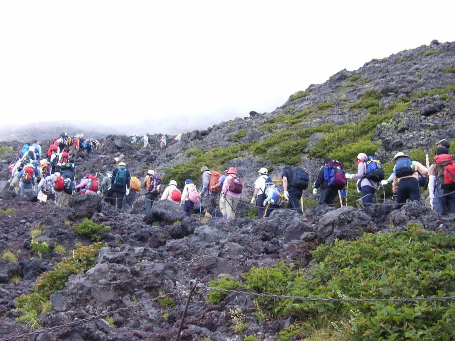 Hikers backed up crossing a rocky area near the 7th station
